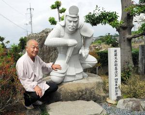 没後400年の昨年に設置された後藤又兵衛像と友澤良謙住職=伊予市宮下の長泉寺