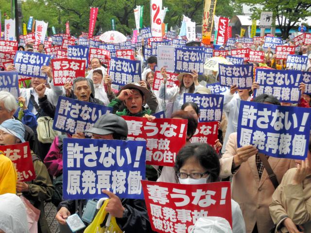 プラカードを掲げて脱原発を求める参加者ら=22日午後2時40分、東京都渋谷区の代々木公園、工藤隆治撮影