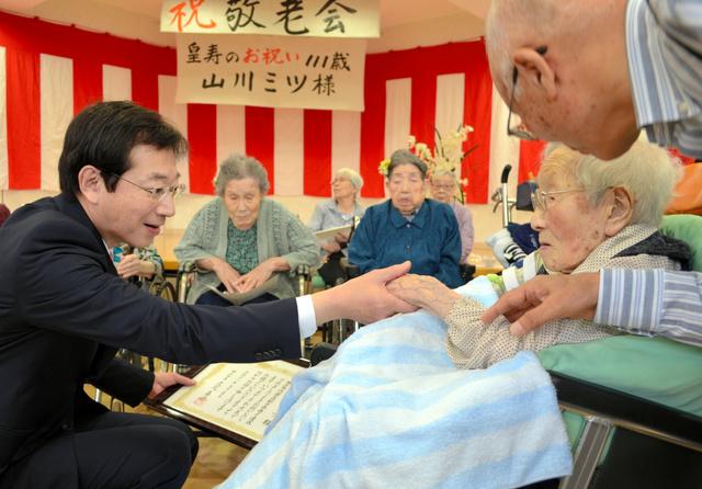 山川ミツさん(右)の手を取って、祝いの言葉を伝える久元喜造市長=神戸市須磨区神の谷5丁目の特別養護老人ホーム「宙カミーノ」