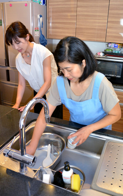 永名聡弓さん(左)宅に派遣され、台所を掃除する家事代行スタッフのソナエ・マリサさん=川崎市宮前区