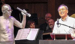 授賞式でスピーチをする東山篤規・立命館大教授。左は授賞式の恒例、懐中電灯を持った照明係「人間スポットライト」を演じるジム・ブレット博士=米マサチューセッツ州、小林哲撮影