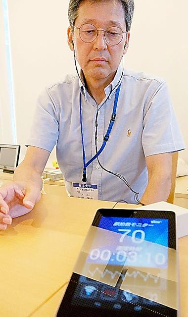 イヤホン状の外耳道内圧測定装置をつけて脈拍数を測定する寺田信幸教授。ノイズが入るので測定中は安静にする必要がある=埼玉県川越市の東洋大理工学部