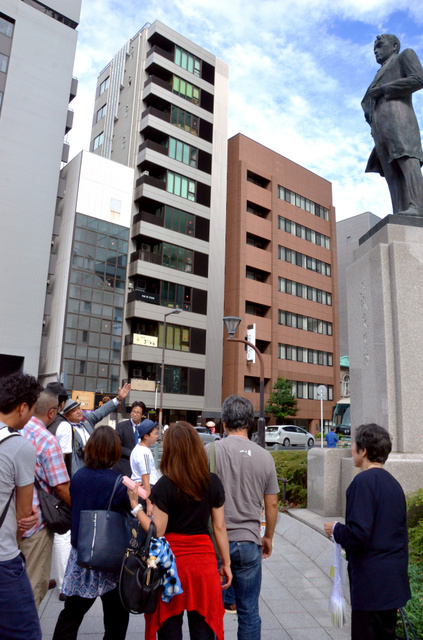ガイドの案内を聞きながら五代友厚像を見上げる参加者たち=25日、大阪市中央区、半田尚子撮影