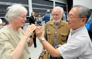 講演後、女性に逆さ眼鏡の使い方を紹介する東山篤規教授(右)=米マサチューセッツ州、小林哲撮影