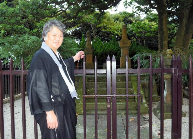 公園の頂上にある三浦按針夫妻の墓の前に立つ浄土寺住職の逸見道郎さん。墓は江戸城の方角を向いているという=神奈川県横須賀…