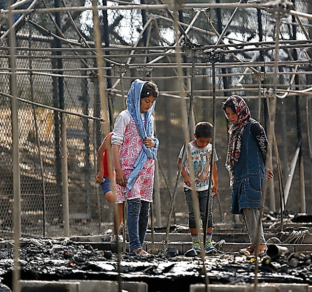 モリア難民キャンプで20日、火災で焼失したテントの横に立ち尽くす難民ら=ロイター