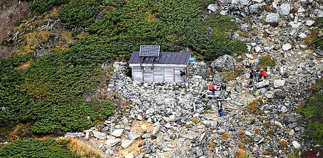 御嶽山王滝口登山道の9合目では、避難小屋の近くで休憩する登山者の姿が見られた=25日午前、本社ヘリから、迫和義撮影