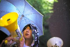 小雨がちらつく中、国会前で安保関連法案に反対する女性=2015年9月18日午後10時23分、関田航撮影
