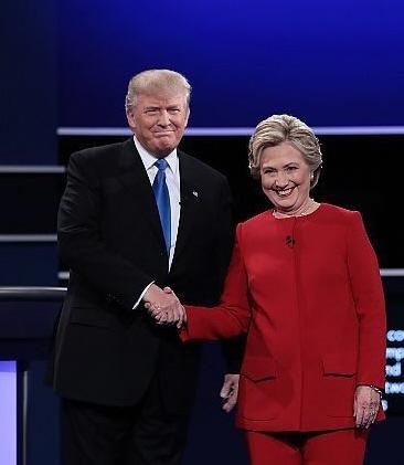 26日、米大統領選討論会で握手をする民主党のヒラリー・クリントン氏(右)と共和党のドナルド・トランプ氏=AFP時事
