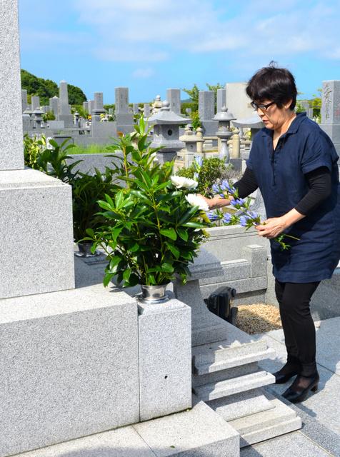 長井健司さんの墓前に花を手向ける妹の小川典子さん=今治市山路