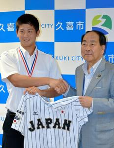 アジア選手権で着用した日本代表ユニホームを手に田中市長と握手する高橋昂也投手(左)