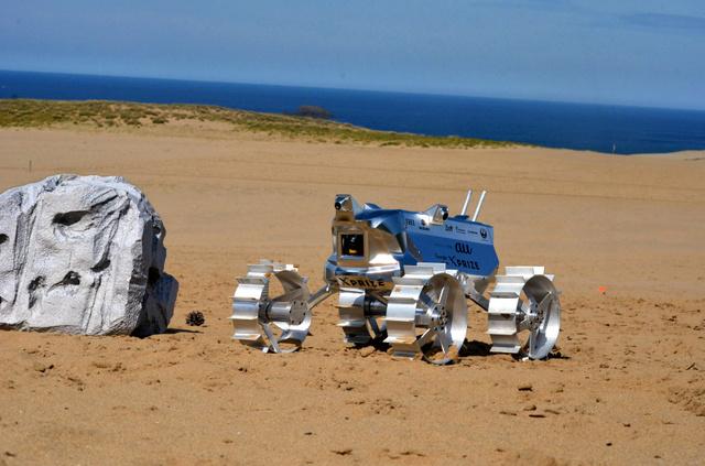 鳥取砂丘を走る月面探査機の試作機(全長60センチ)。試験のため、岩に見立てた障害物も置かれた=鳥取市浜坂