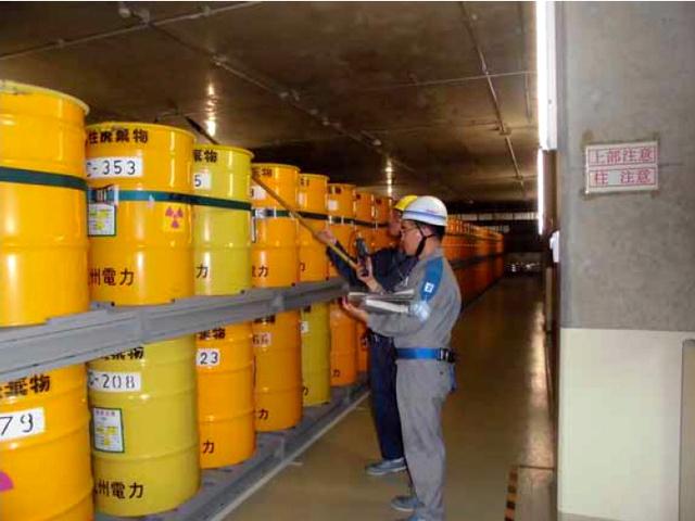 低レベル放射性廃棄物を保管するドラム缶を確認する作業員=鹿児島県薩摩川内市の川内原発、九州電力提供