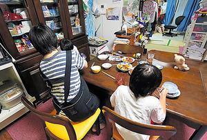 子どもたちの世話をしながら食卓につく神奈川県の女性(左)=池永牧子撮影