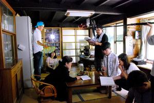映画の撮影風景。韓国からの男子留学生が主人公の女子大生の家族と語り合う場面=千葉県鴨川市