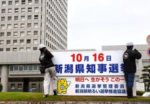 知事選の広告看板を設置する作業員=新潟市中央区