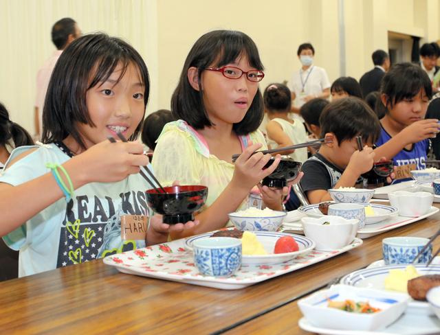 配膳されたハンバーグなどの夕食を食べる子どもたち=北九州市八幡東区の尾倉市民センター