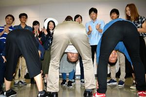 学生と股のぞきをする東山篤規・立命館大教授(中央)=京都市の立命館大