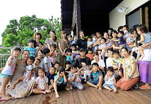 2012年、沖縄県の久米島に完成した球美の里で、保養に訪れた福島県の母子と記念撮影(中央の帽子姿)=本人提供