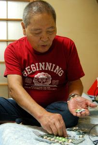 石綿疾患の症状を抑えるため、20錠ほどの薬を毎日服用しているという八木千年さん=22日、鹿児島市吉野町