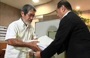 住民投票条例制定の本請求で、2349人の署名を岩川浩一副町長(右)に渡す松田正代表=屋久島町