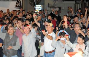 午後6時、一斉に杯を掲げる人々=会津若松市役所前