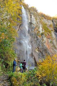 米子大瀑布のひとつ、不動滝と周辺の紅葉を楽しむ人たち=2015年10月、須坂市
