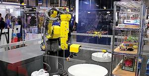プリファード・ネットワークスが展示しているロボット。棚から物を取り出して、指定された場所に置く=千葉市美浜区