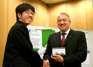 銅板の折り鶴を贈り、握手する広島市立広島工業高校の生徒(左)とペーター・コラロフ団長=広島市中区