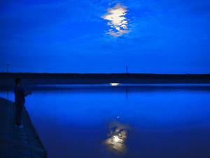 人工池の「横山池」。月明かりに照らされた水面に、釣り人がルアーを投げていた=津市芸濃町