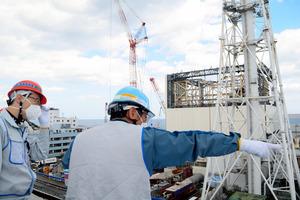 壁カバーの撤去作業が進む1号機原子炉建屋などを視察する内堀雅雄知事(左)=東京電力福島第一原発、代表撮影