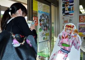 アニメキャラクターのパネルの前で写真を撮るスタンプラリー参加者