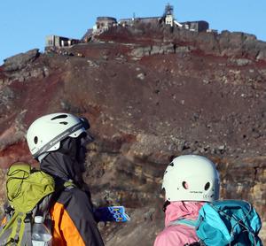 山頂付近のヘルメット姿の登山者。外国人グループはかぶったり、携帯したりしていた=8月10日、富士吉田市の吉田口登山道