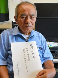 「70年史」を手に被爆体験を継承する大切さを訴える音丸篤夫さん=三原市円一町2丁目