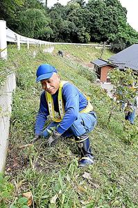 住民からの依頼を受け、草刈り作業をする東京電力社員の山本義弘さん。依頼者は来春にも一家で帰還しようと考えている=福島県楢葉町