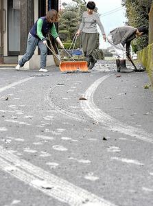 未明に36年ぶりの爆発的噴火が起き、自宅前を掃除する人たち=8日午前7時35分、熊本県阿蘇市、福岡亜純撮影