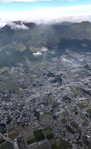 噴火で降った灰で包まれた市街地。中岳(中央奥)は雲に隠れ見えなかった=8日午前、熊本県阿蘇市、本社ヘリから、森下東樹撮影