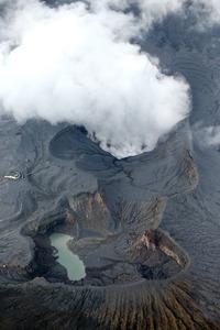 爆発的噴火から一夜明けた阿蘇山。中岳火口からは白煙が立ち上り、周囲は火山灰で覆われていた=9日午後3時38分、熊本県阿蘇市、朝日新聞社ヘリから、河合真人撮影