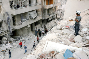 シリア北部アレッポの反体制派掌握地域の近郊で4日、政権軍の空爆後、救出作業のため崩壊した建物に立つシリア民間防衛隊員=AFP時事