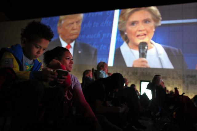 クリントン氏とトランプ氏の討論会の中継をパブリックビューイング会場で見る人々=9日午後8時17分、米セントルイス、矢木隆晴撮影