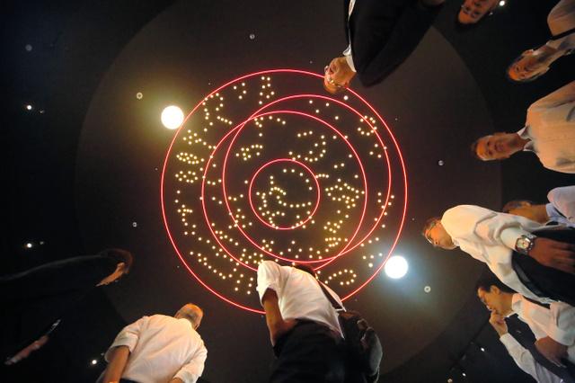 「四神の館」の天井に映し出されたキトラ天文図を見上げる人たち=奈良県明日香村