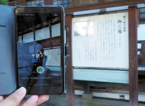 阿弥陀寺の「御三階」の説明板の前にスマートフォンをかざすと、土方歳三が登場する=会津若松市七日町