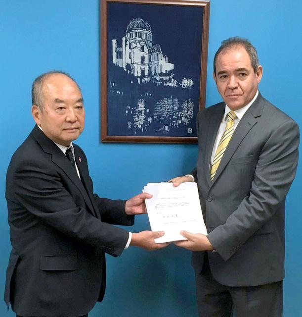 国連総会第1委員会のブカドゥム議長に署名を手渡す藤森俊希・日本被団協事務局次長(左)=国連のホームページから