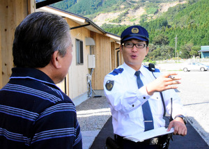 立野駐在所管内の住民が暮らす仮設住宅を訪ねて話す真崎巡査部長=南阿蘇村、板倉大地撮影