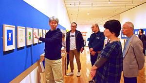 ギャラリートークで、初版本の原画を前に裏話などを披露する森本俊司次長(左)=益田市有明町