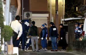 女性が刺された現場付近を調べる捜査員=15日午後9時47分、福岡市南区南大橋1丁目