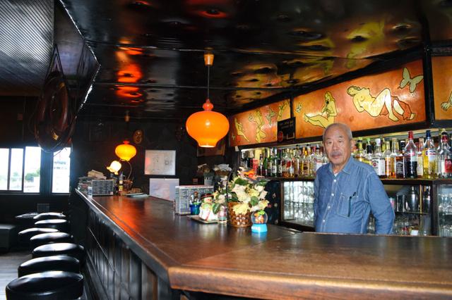 カウンターに立つ林彰男さん。壁と天井は革張りだ=横浜市神奈川区千若町2丁目