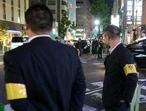 今年5月の取り締まりの様子。黄色い腕章の捜査員が姿を現すと、客引きは動きを止めた。捜査員の問いに、客引きたちは「休憩」「連れ待ち」などと答えていた=名古屋市中区錦3丁目