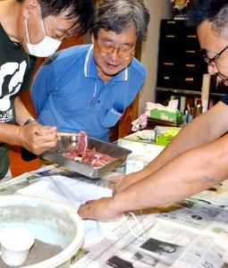シシ肉の灰干しの試作を指導する干川剛史教授(中央)=熊本県南阿蘇村河陽