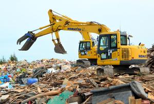 仮置き場に運び込まれた災害廃棄物の選別が進む=久慈市